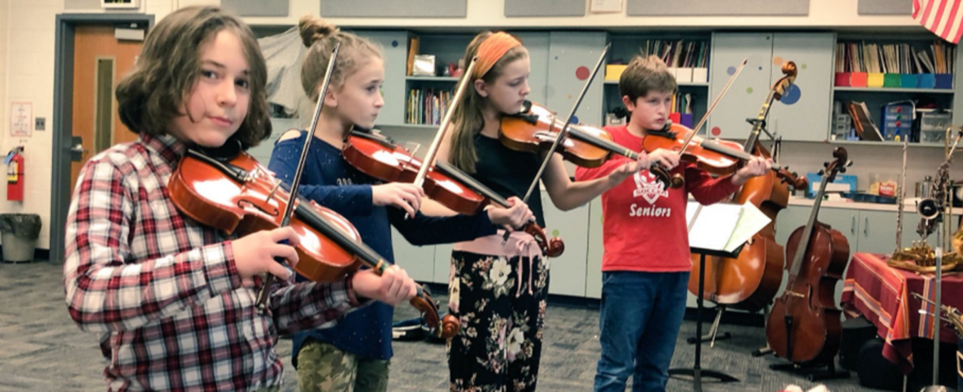 Four student violinists practicing
