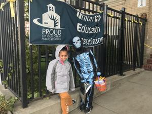 A blue skeleton and student outside school