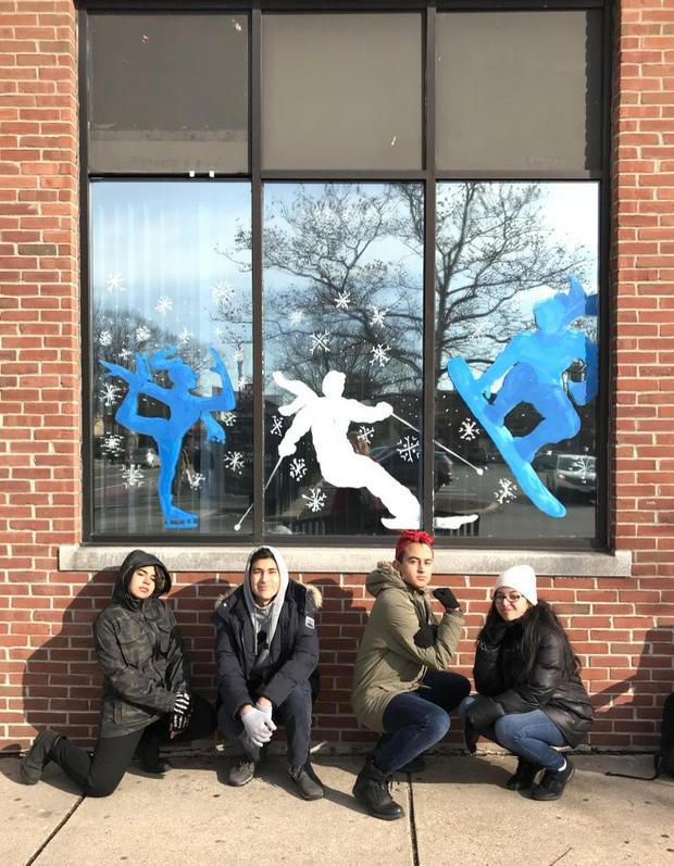 Four students kneel beneath a window they decorated with images of a skater, a skier, and a snowboarder