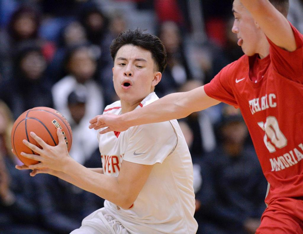 A player keeps the basketball away from a close defender