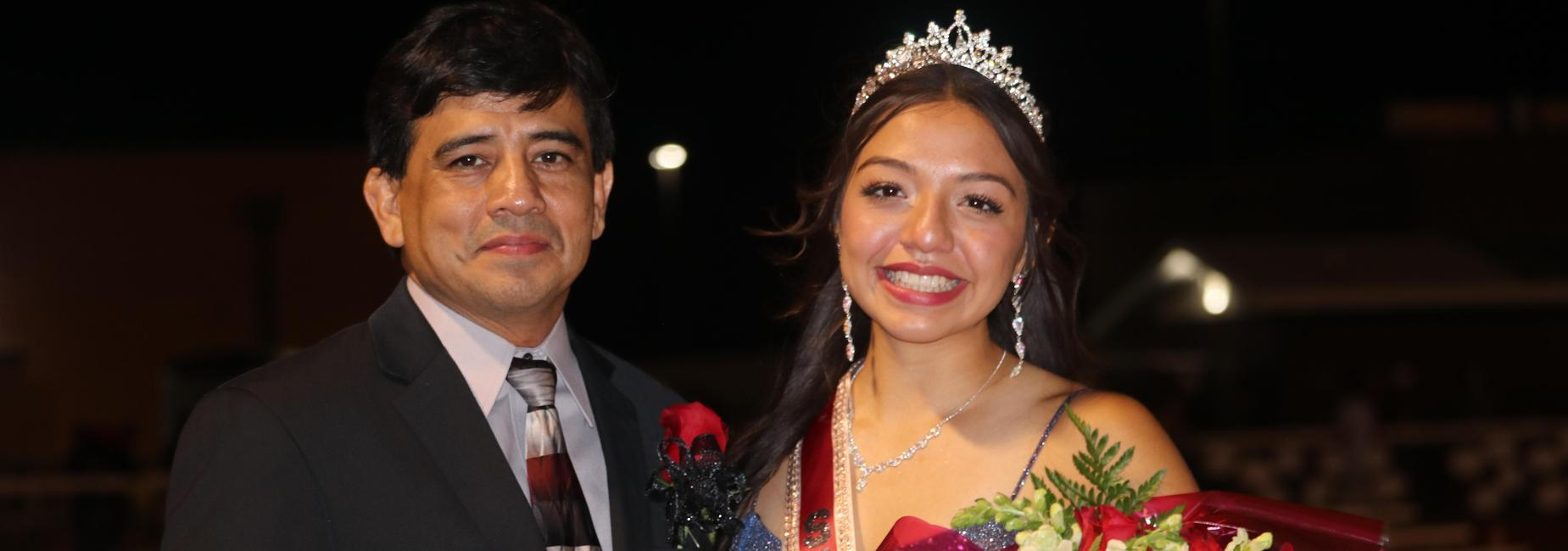 Homecoming queen smiles next to her dad