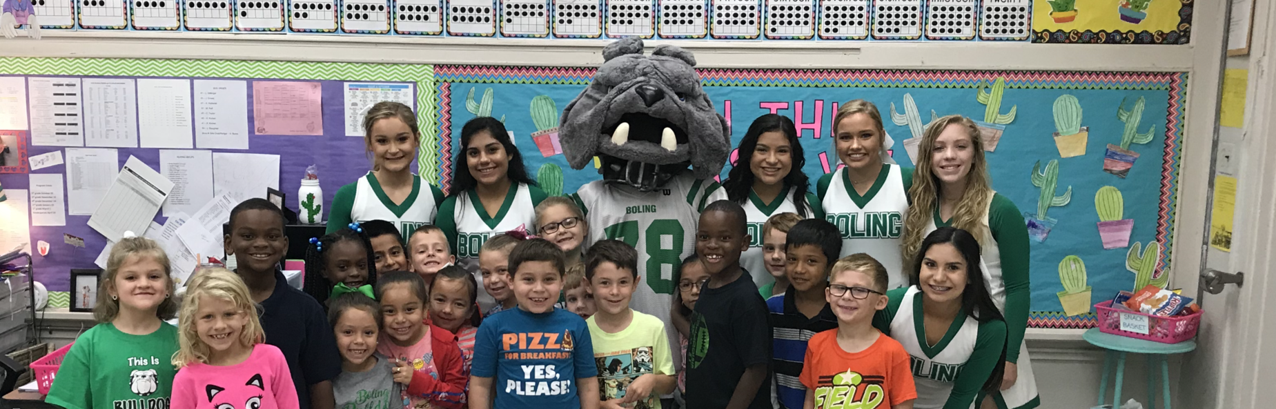 a group of elementary school children with high school cheerleaders and bulldog mascot