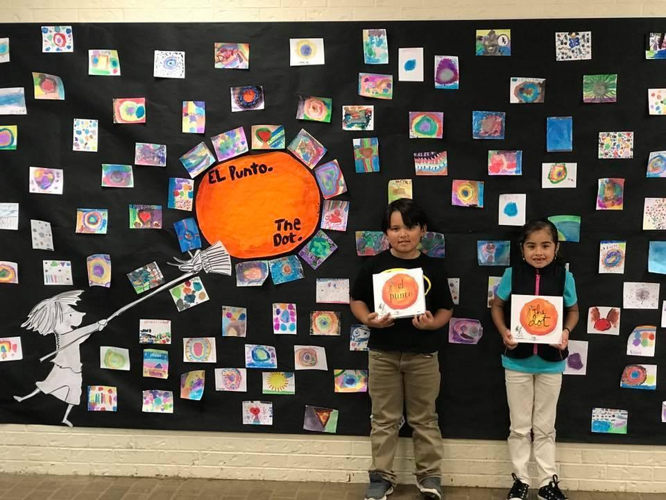 two students standing with their artwork