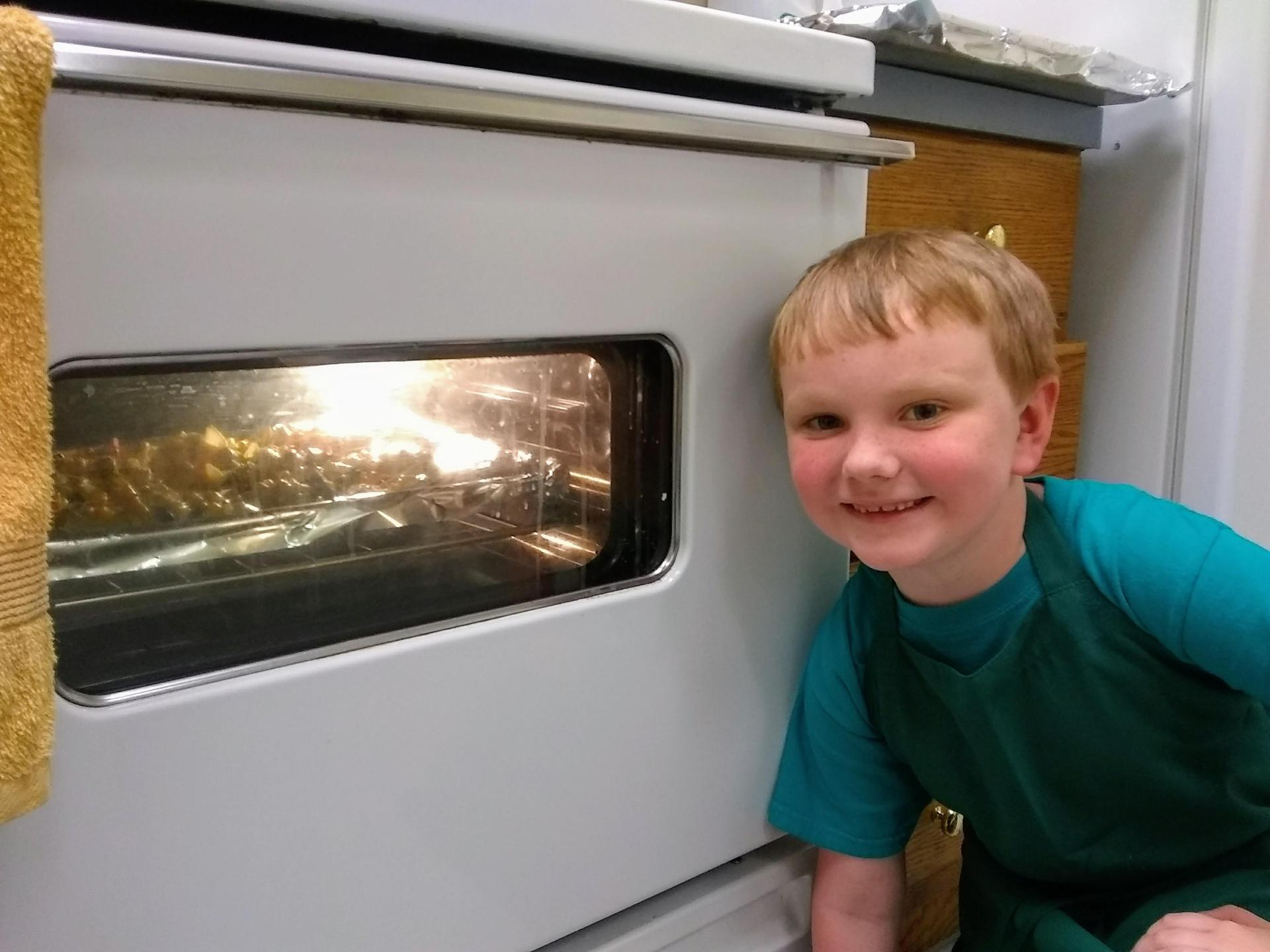 kids watching their chicken cook in oven