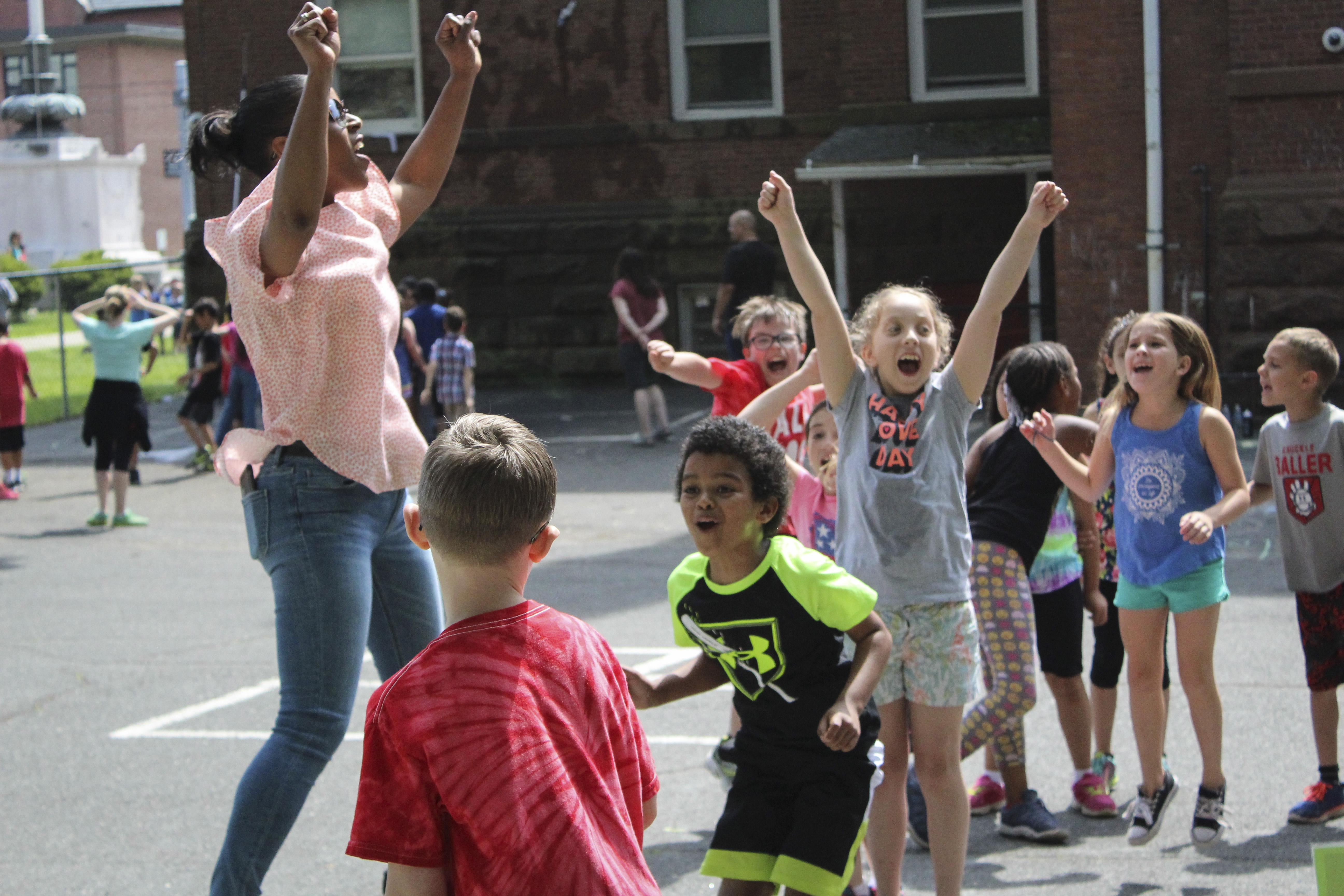 Parent celebrating with students on playground