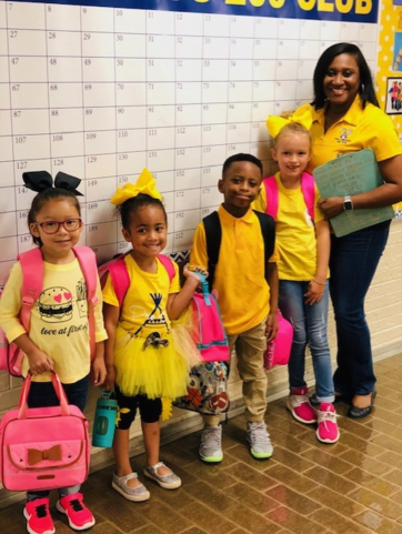 Kids and teacher dressed in all yellow for Homecoming Week