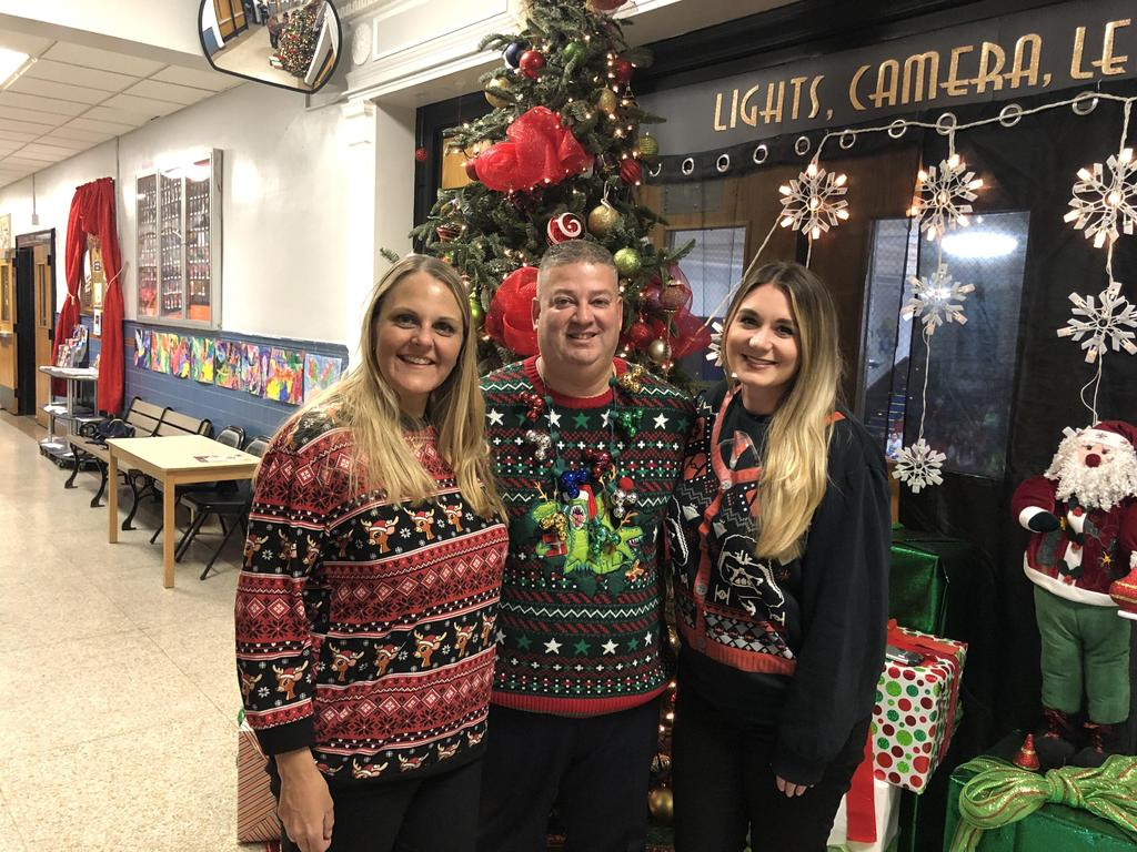 Ms. Mullaly, Principal Rivera, and Supervisor Abbatto wearing ugly sweater in the entryway in front of the school