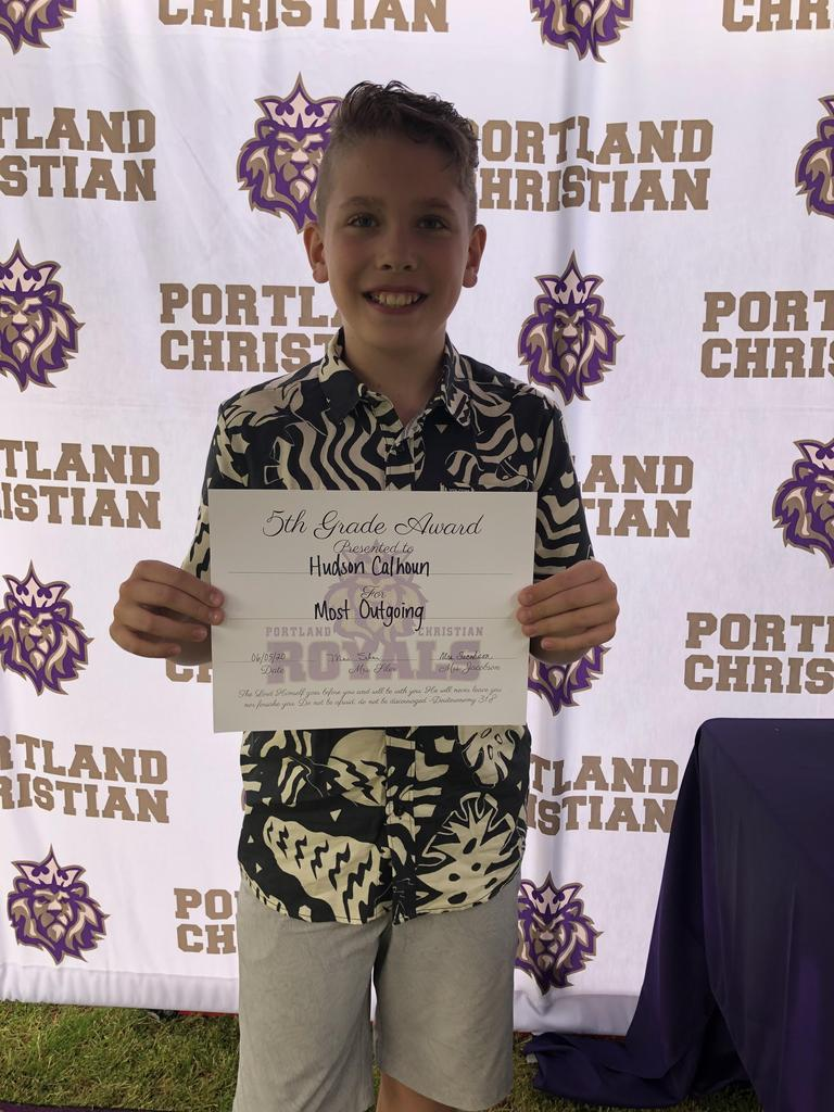 Fifth grader posing in front of PCS backdrop