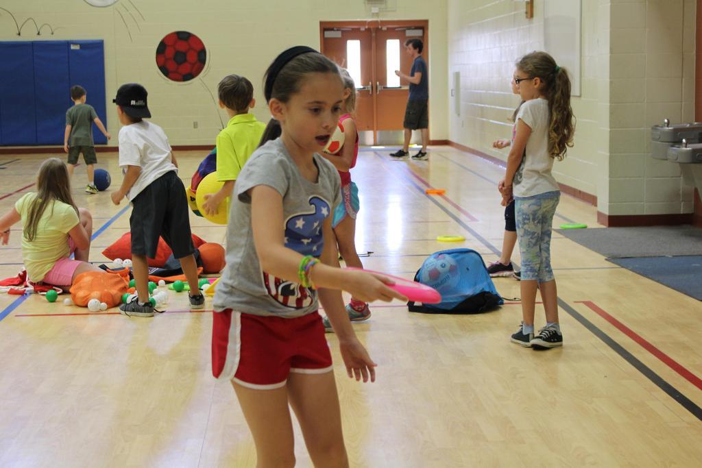 Giving it a whirl! Skye Idskou tries frisbee-throwing during Camp Good Sam recreation time in the Jacob's Well Elementary School Gymnasium.