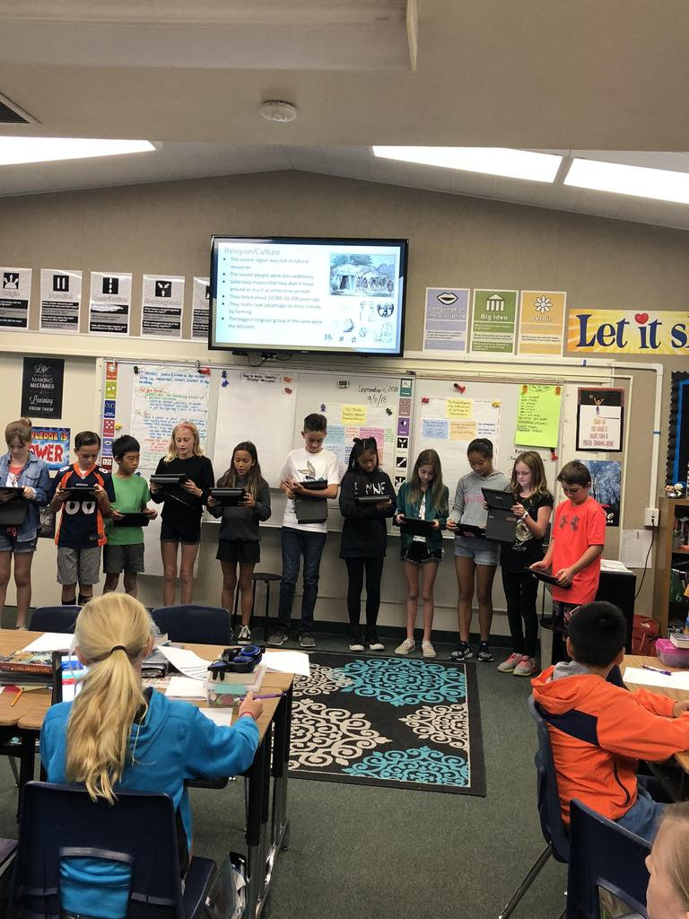 Sixth graders standing at the front of the class with their ipads