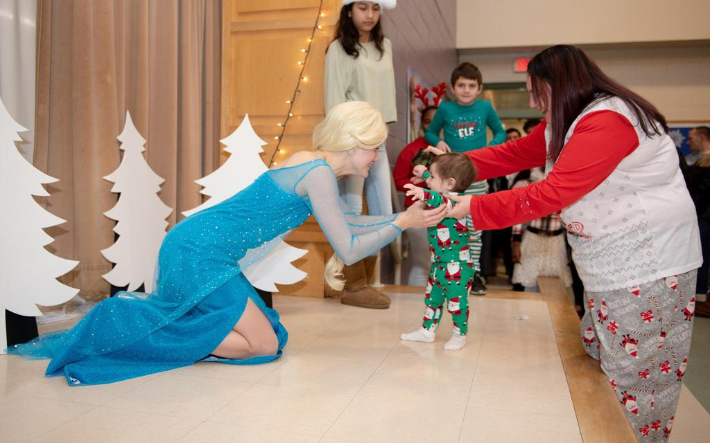 """Elsa from """"Frozen"""" reaches towards a toddler who's being helped to walk across the stage"""