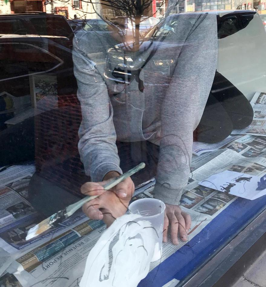 A student is pictured through a window, into a business, as he works on a design on his hands and knees