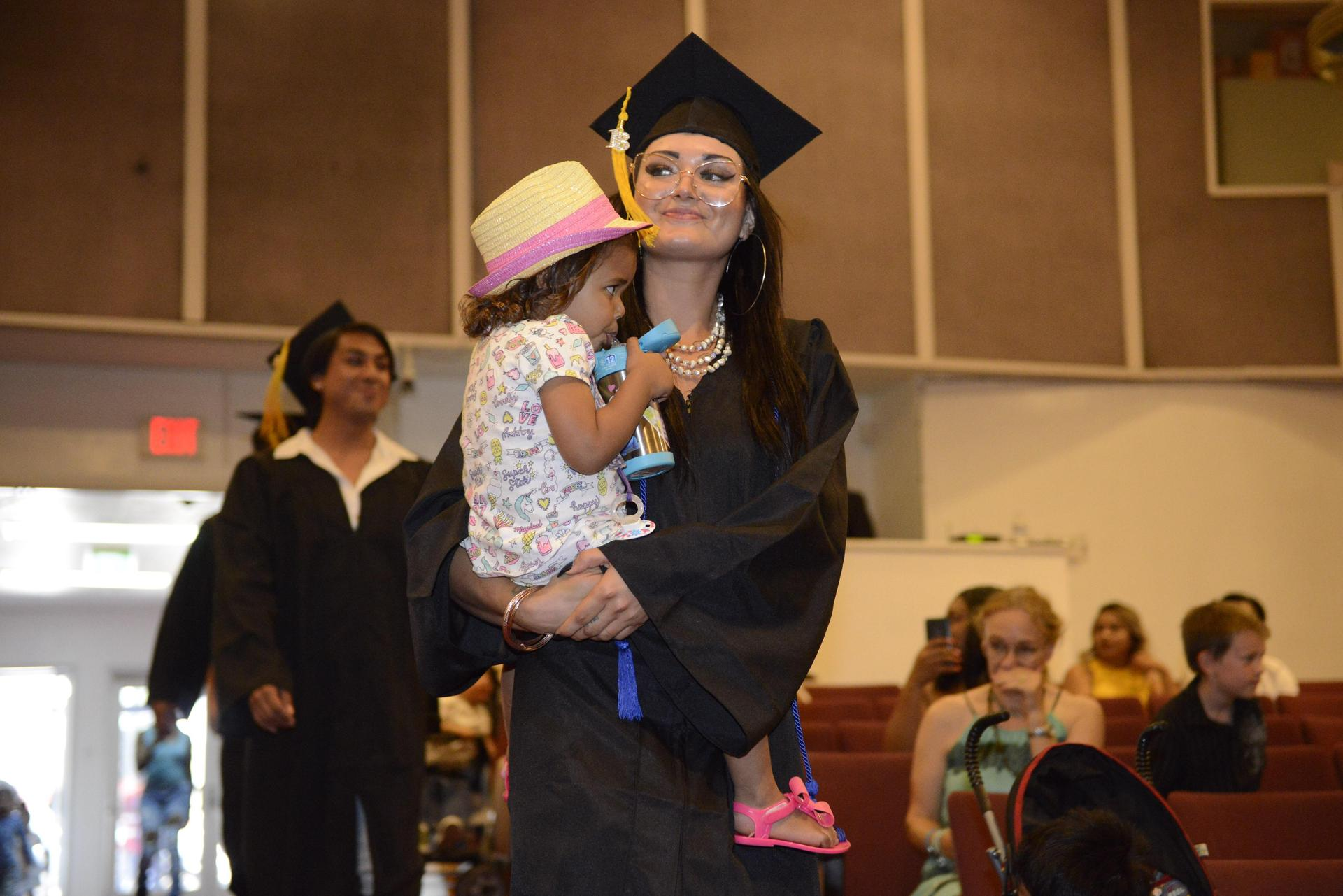 A 2018 grad holds her baby