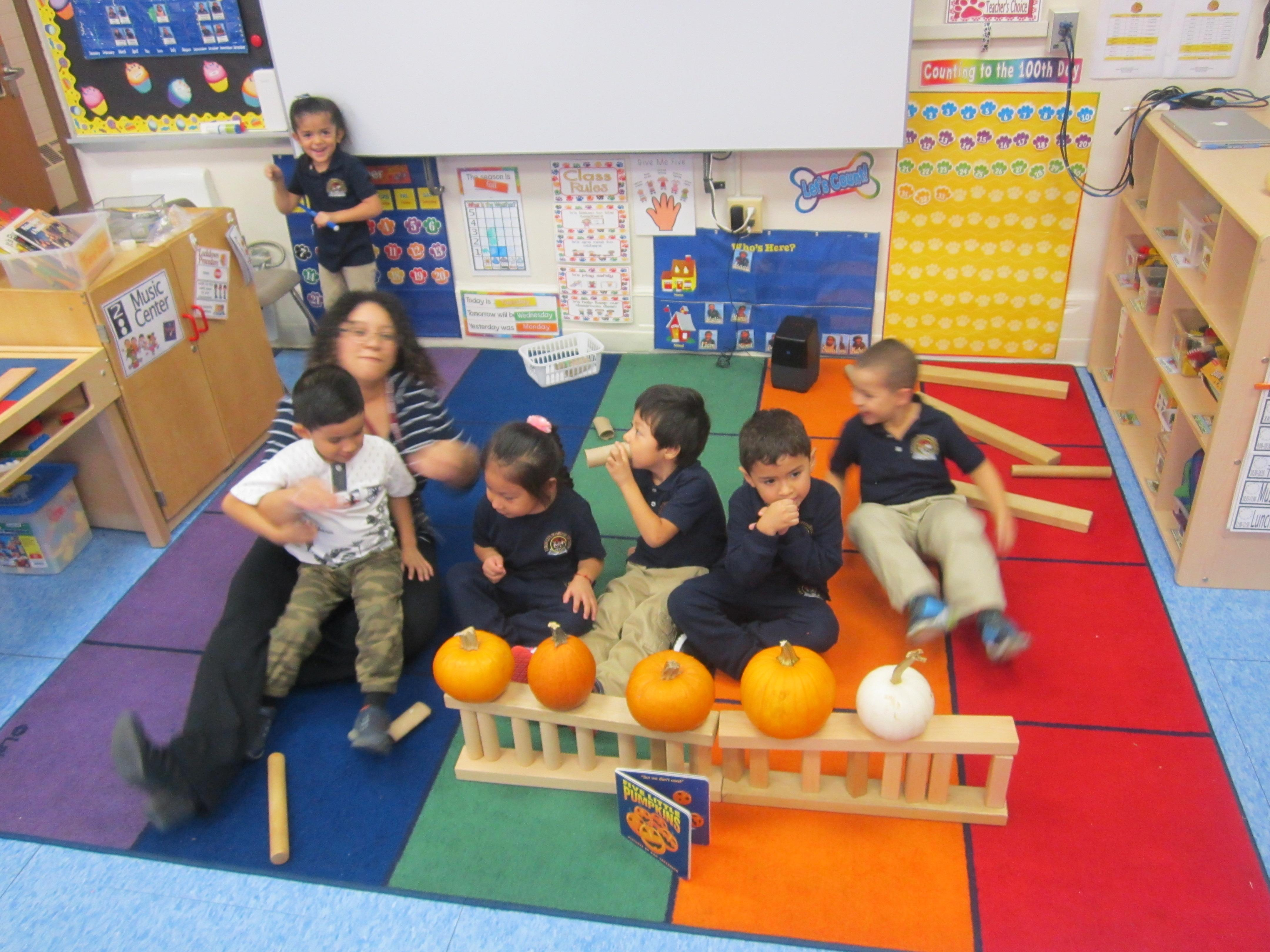group of students building a life size structure with real pumpkin as teacher looks on