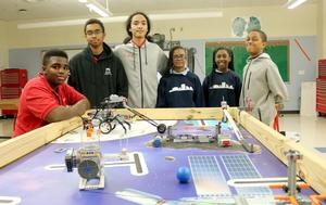 The KCCA robotics team stands around a table that has their robot car for the competition