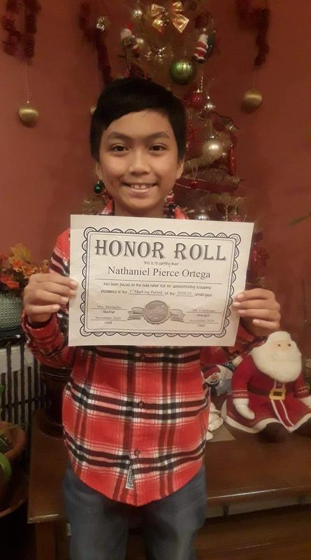Nathaniel holding honor roll certificate