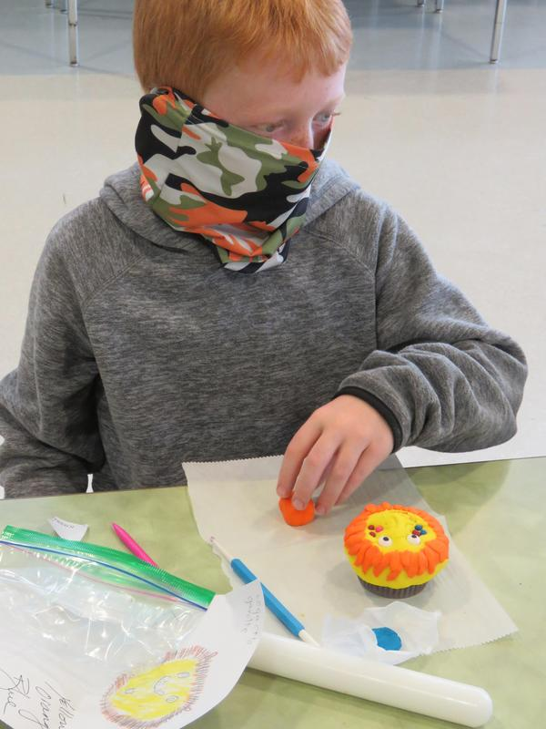 A student works on a lion design on his cupcake.