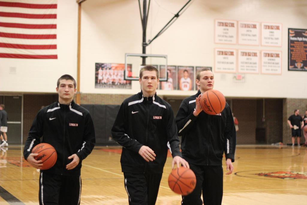 Three basketball players warming up on the court