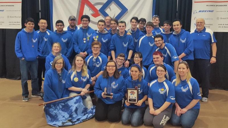 High School Robotics Team dressed in blue shirts holding their awards, a plaque and a crystal award.