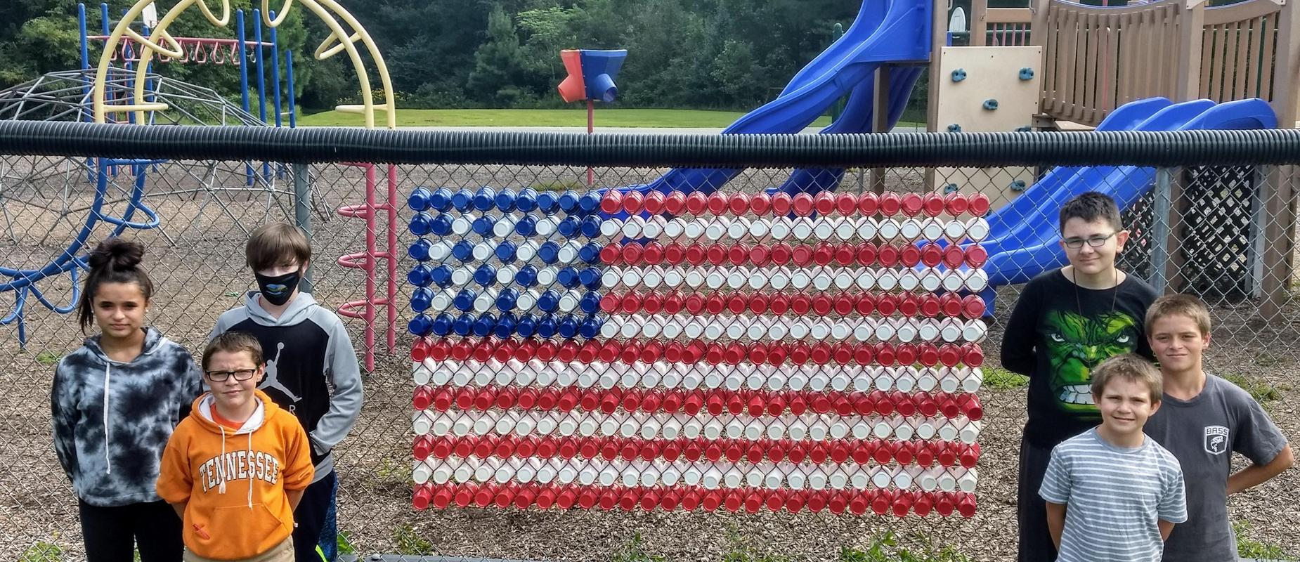 students made an american flag out of plastic cups on the playground fence
