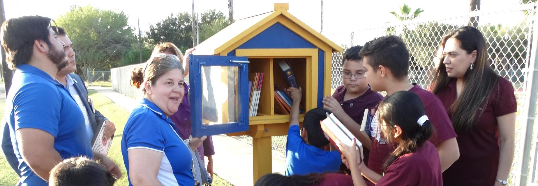 Students and staff placing books in the new Little Library