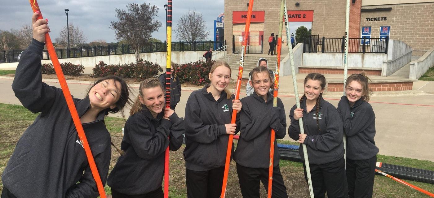 8 female pole vaulters pose together outside with their poles
