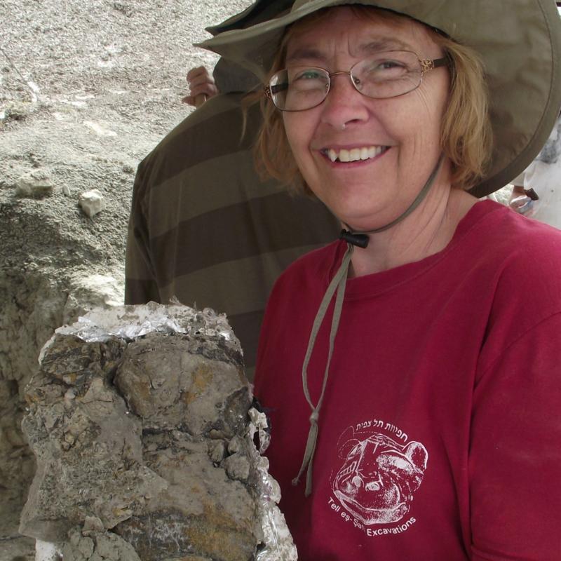 woman poses with a dinosaur bone
