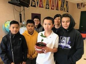 a group of six students with one holding a potted plant