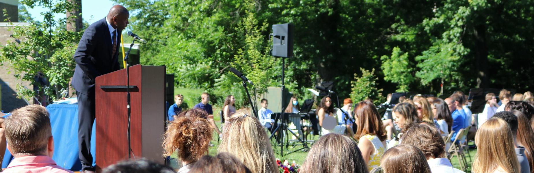 Photo of Roosevelt asst principal Keith Brunson addressing 8th graders and families during promotion ceremony