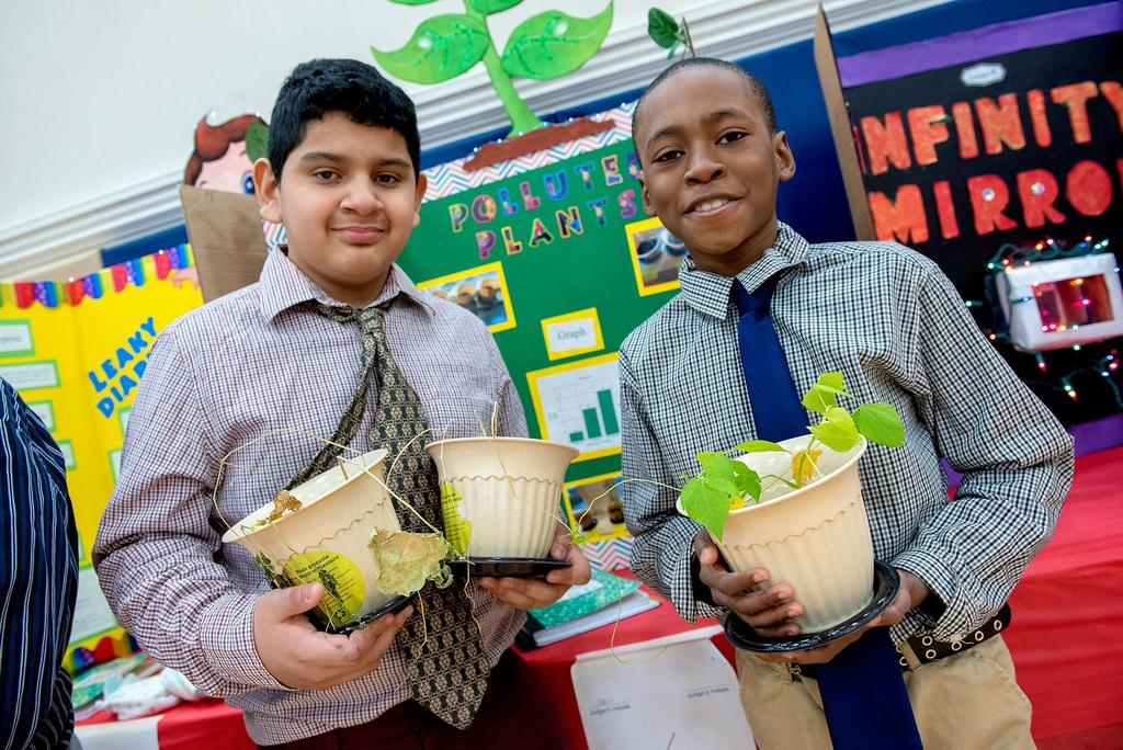 Two students hold pots of plants