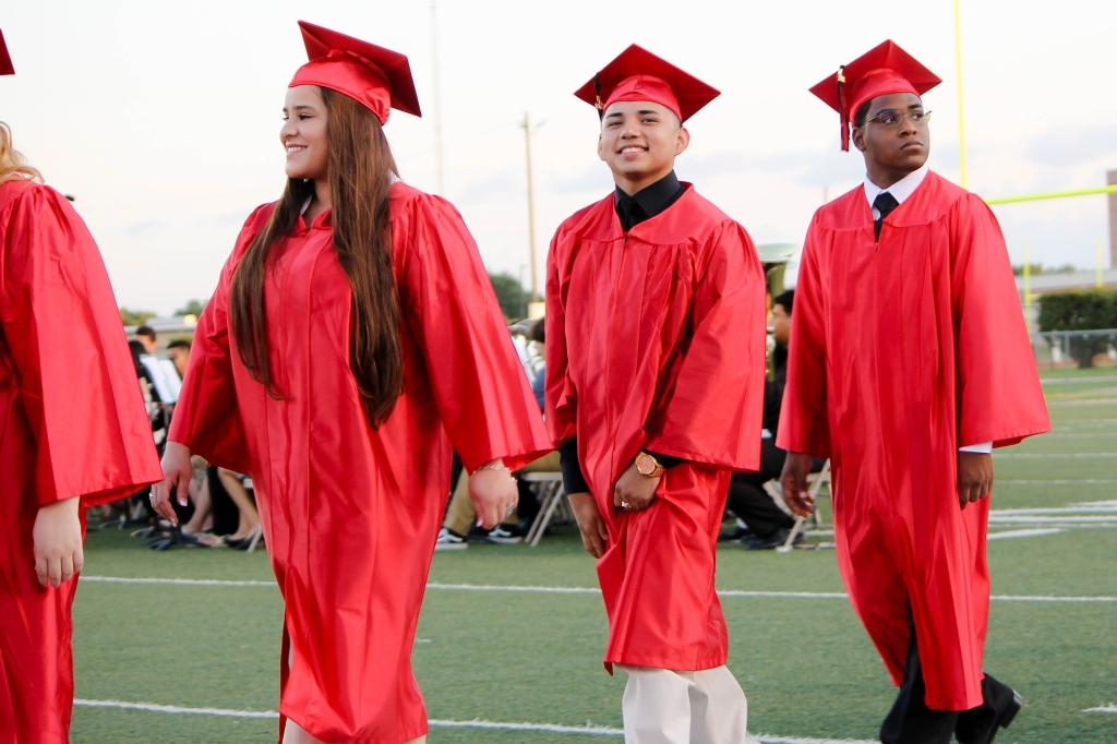 students of the victoria east high school 2018 graduating walking into memorial stadium, smiling male and female student