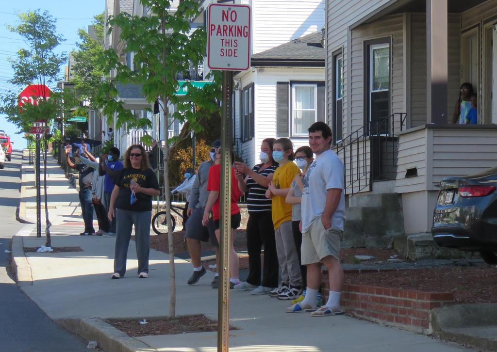 Residents on a sidewalk, taking photos and waving to the passing cars