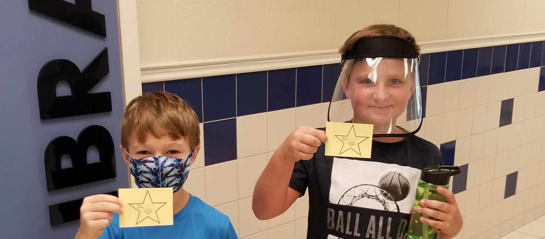 2 boys wearing masks showing their stars they earned