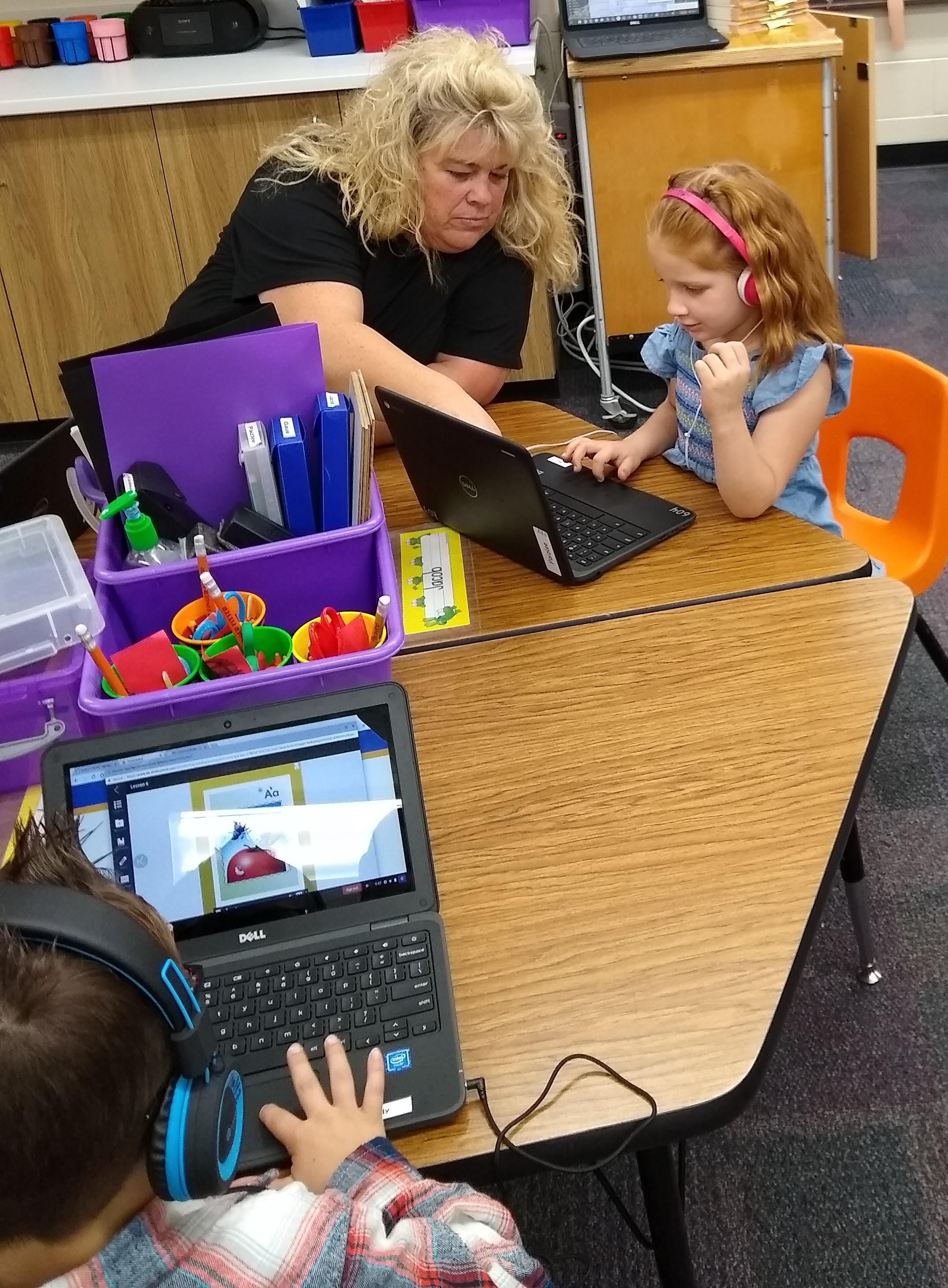 Mrs. Roberts listens to her student read along online.