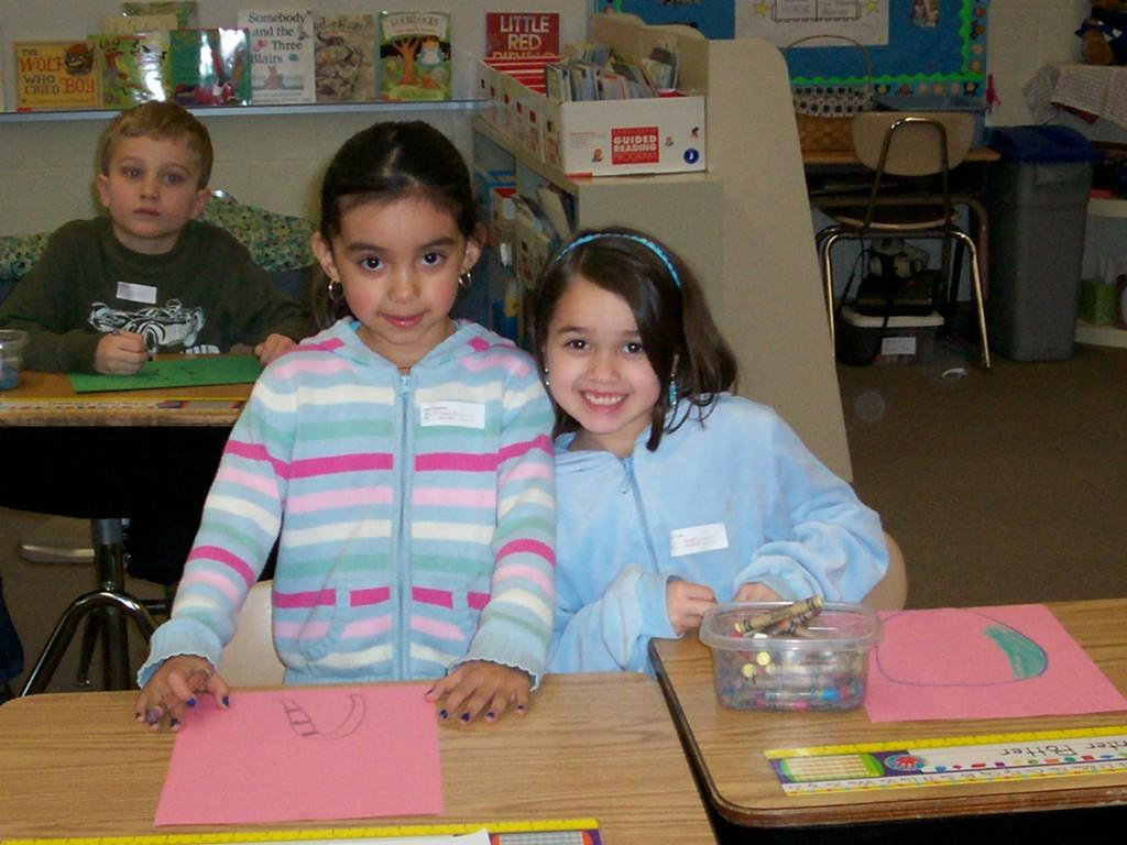 two girls smile for camera while coloring