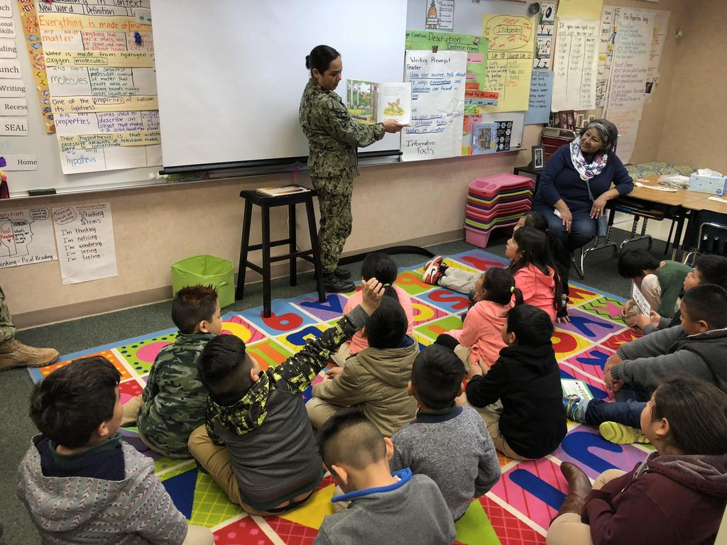 Navy officer reading to students