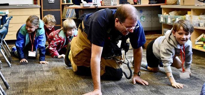 Firefighter demonstrating crawling below smoke