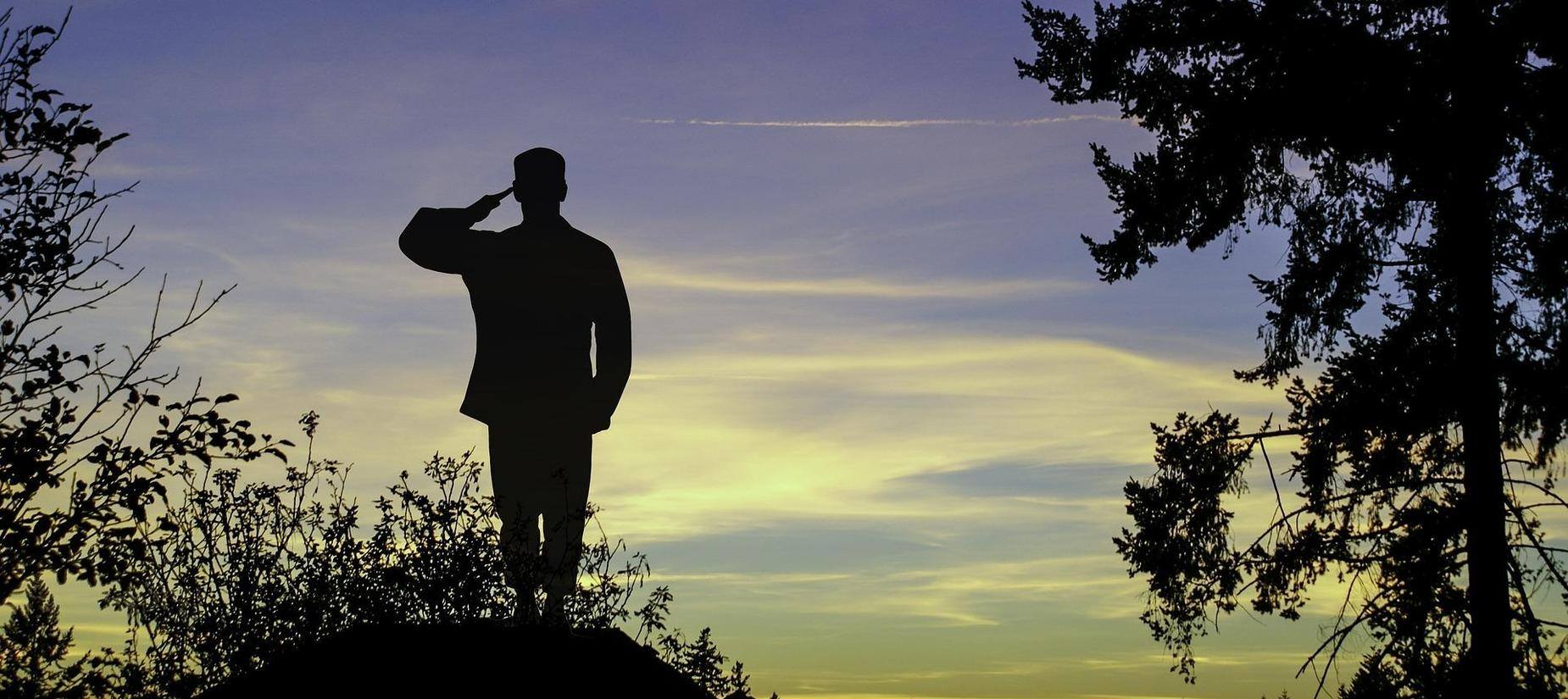 silhouette of a solider with the bright blue sky around him