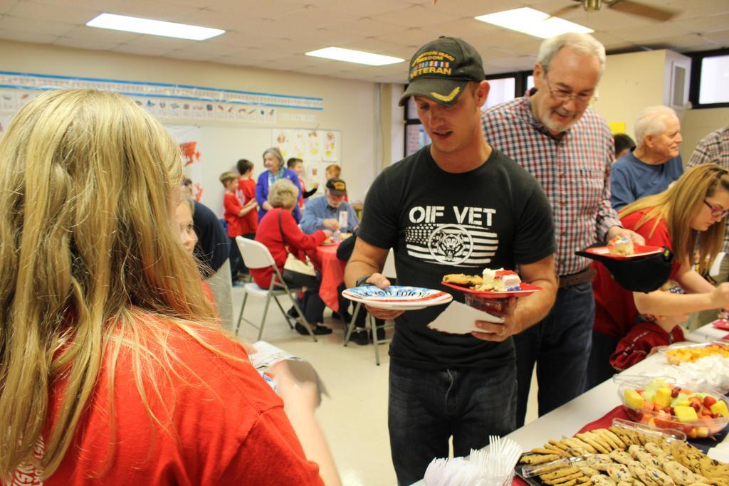 student handing veteran a plate