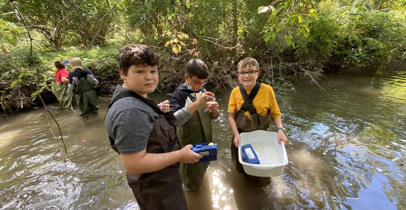 Middle school science students study insects in the nearby creek.