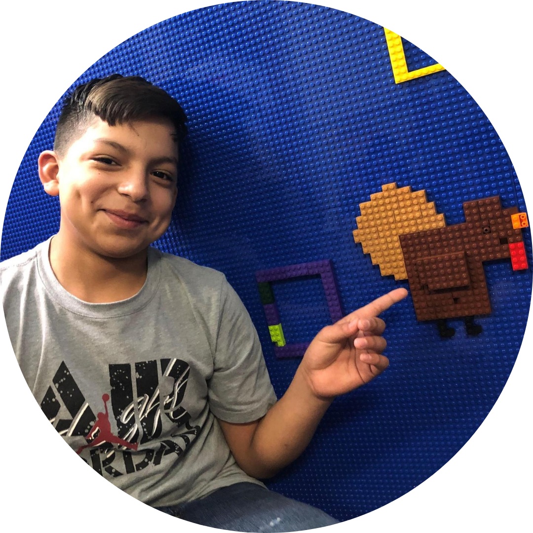 boy pointing to turkey created on a lego wall