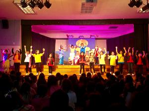 Students performing Aladdin on stage.