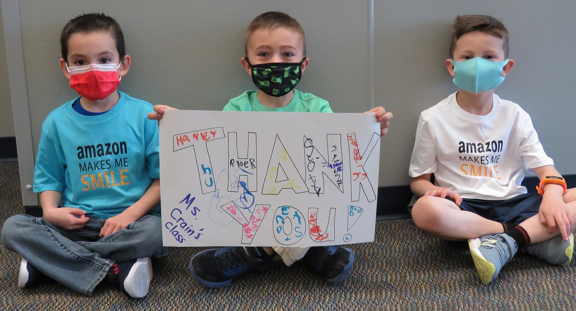Three young boys sit cross-legged while holding a Thank You sign drawn by their class.