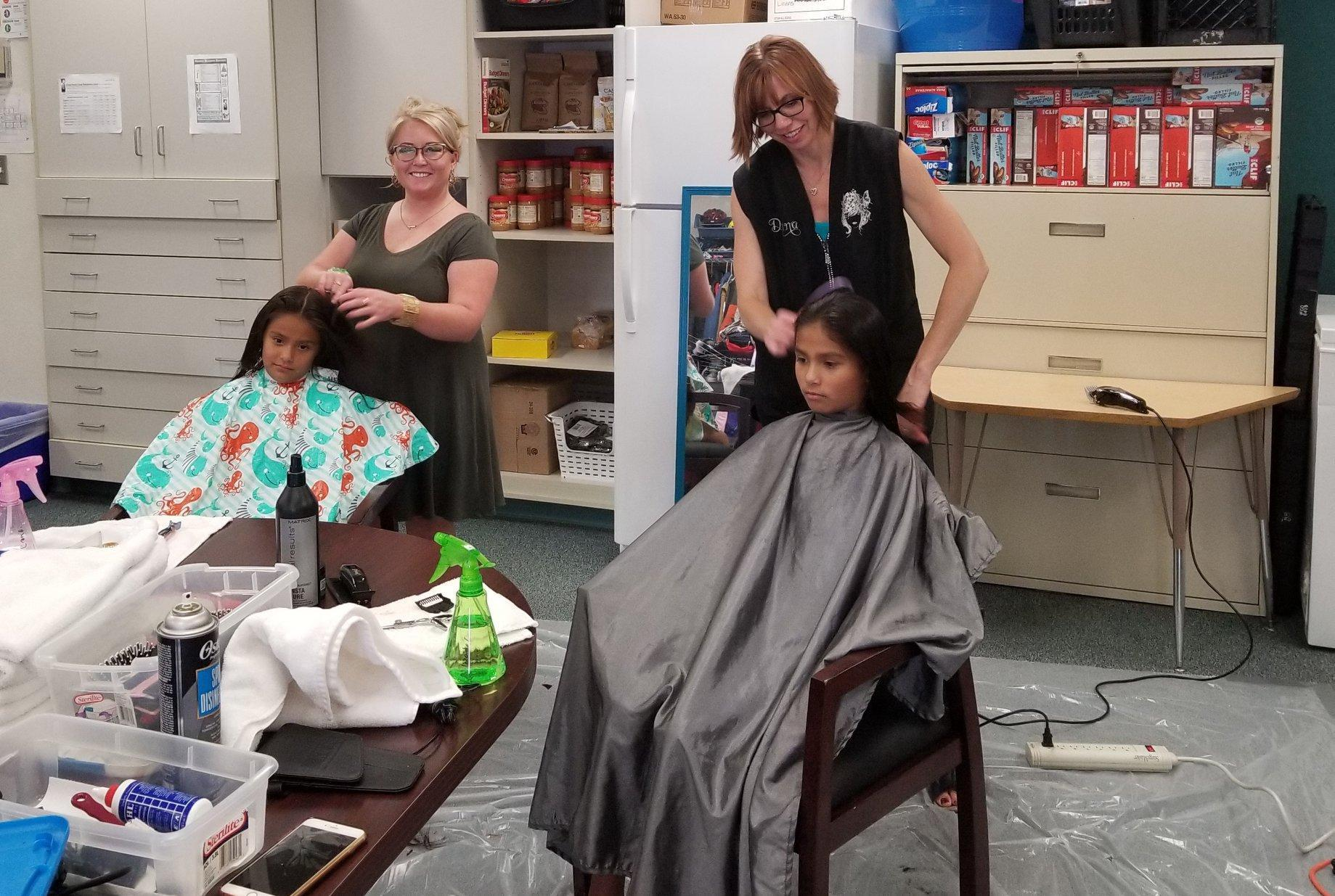 Two girls receive haircuts at the Snake River Family Community Resource Center.