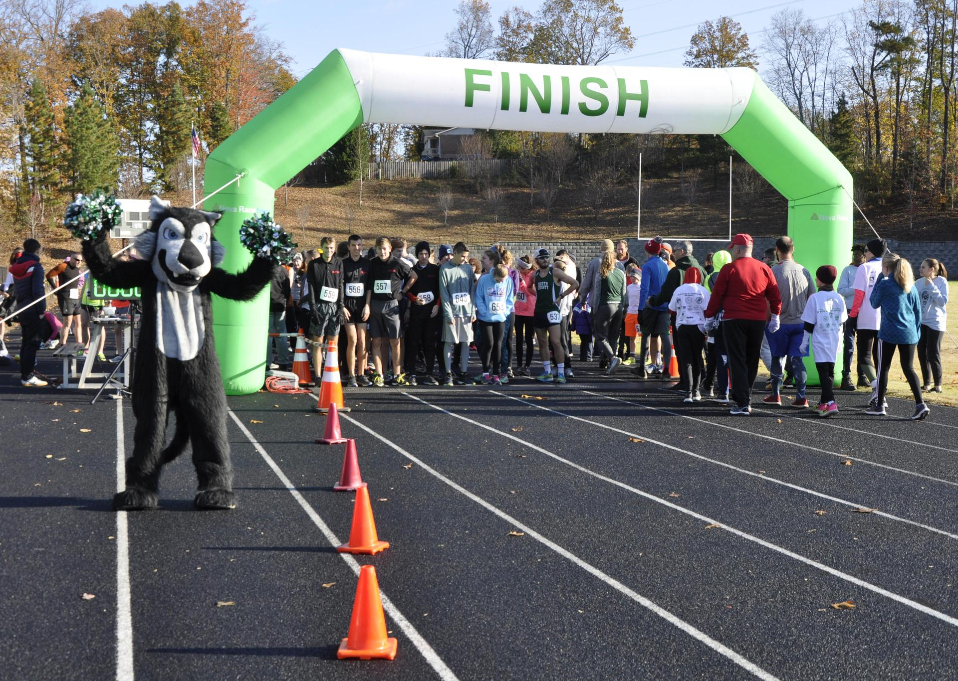 The school mascot cheers on the runners of the JP5K