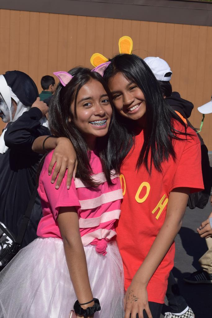 Two students posing for a picture in their costumes.