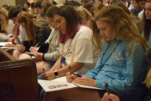 TEENS WRITING WHILE SITTING IN CHURCH PEWS