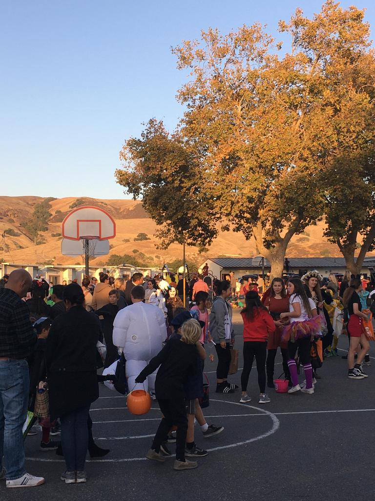 people on blacktop for trunk or treat