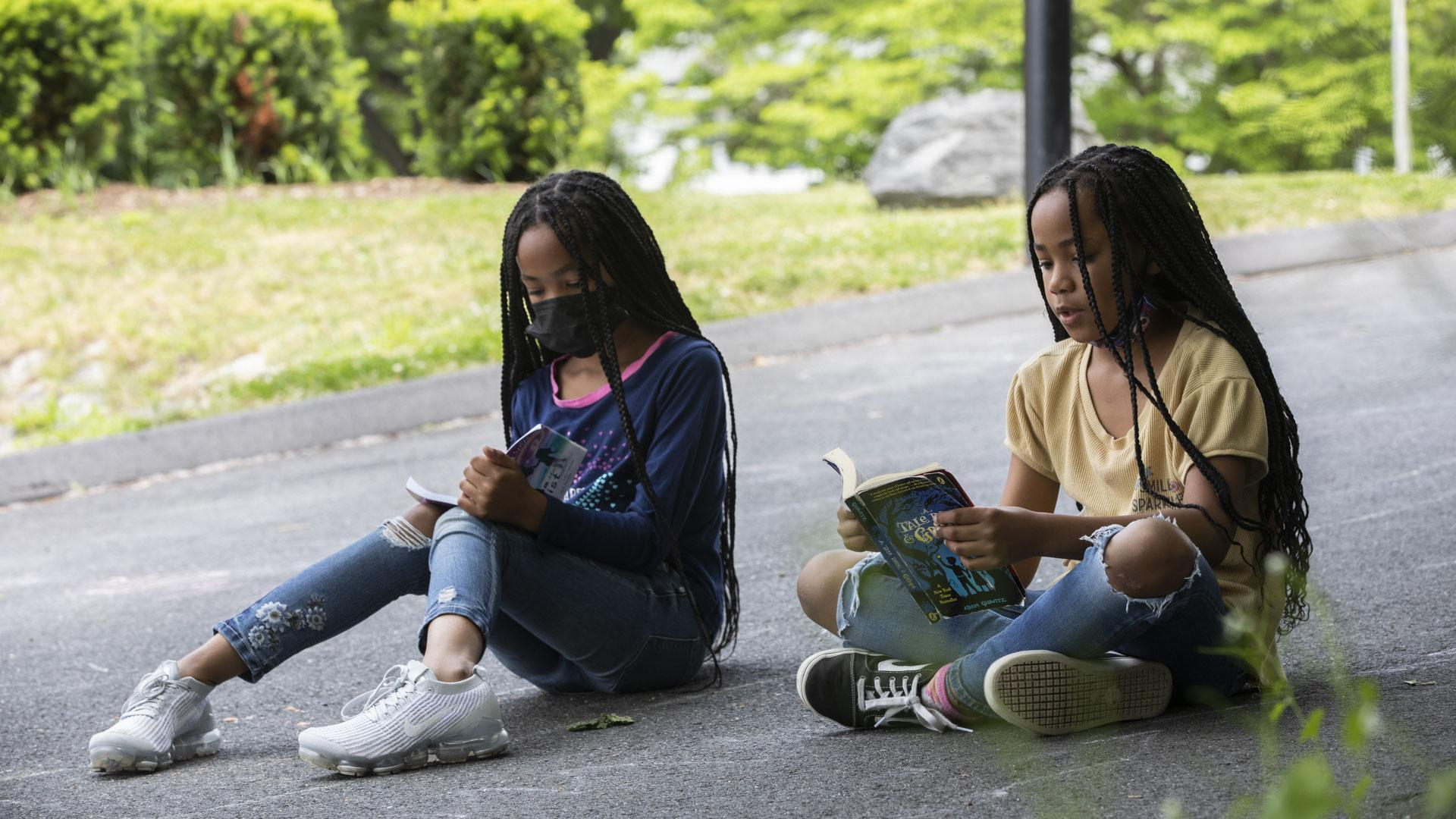 Two girls reading outside.