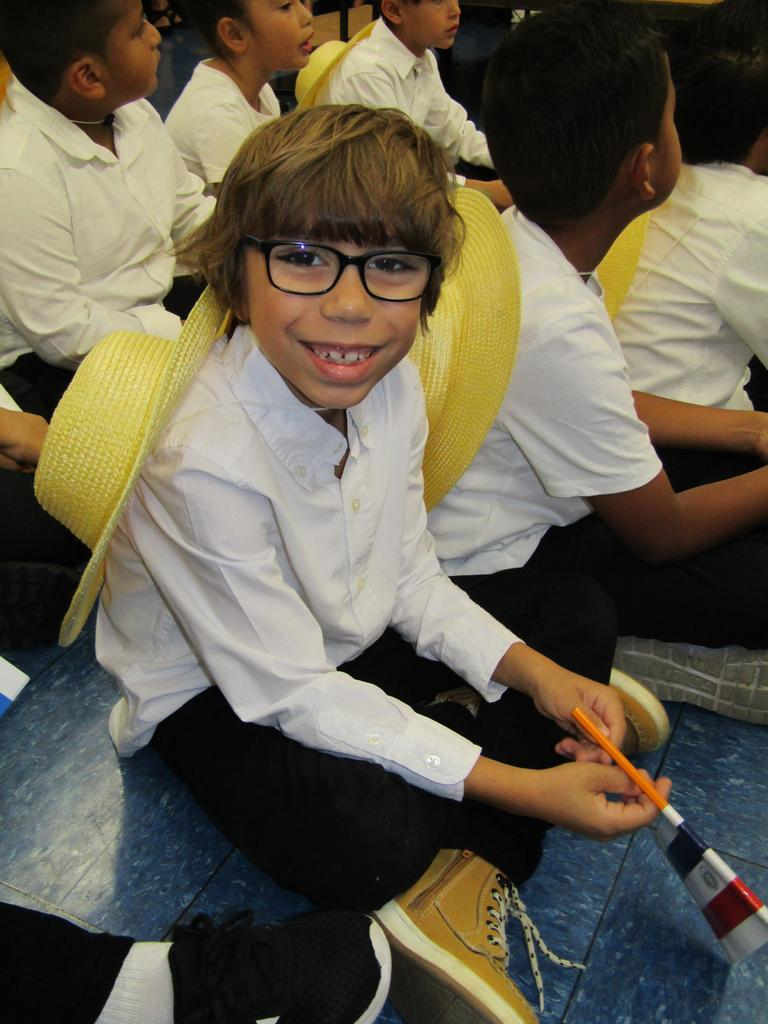 close up of a boy with glasses sitting on the floor